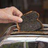 Pane tostato bruciato schioccando dal tostapane fotografia stock libera da diritti