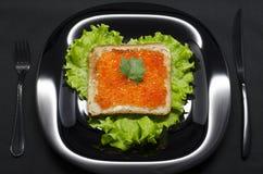 Pane tostato con il caviale rosso e l'insalata verde fotografia stock