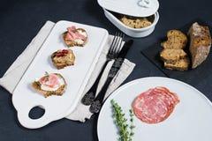 Pane tostato con il pat? di Parma, del salame e dell'oca su un tagliere bianco immagine stock libera da diritti
