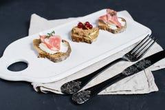 Pane tostato con il pat? di Parma, del salame e dell'oca su un tagliere bianco fotografia stock