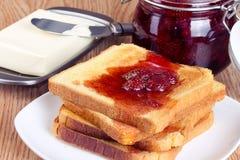 Pane tostato con l'inceppamento ed il burro di fragola Fotografie Stock