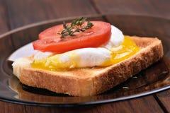 Pane tostato con la fetta del pomodoro e dell'uovo affogato Immagine Stock