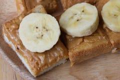 Pane tostato con la fetta della banana e del burro di arachidi Immagini Stock Libere da Diritti