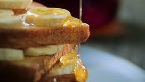 Pane tostato croccante casalingo fresco con miele e le banane sul piatto blu Prima colazione squisita archivi video