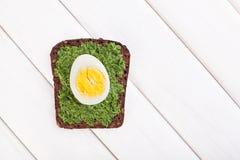 Pane tostato degli spinaci e dell'uovo su bianco Immagine Stock