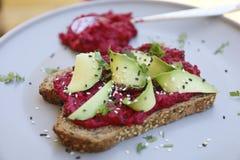 Pane tostato del vegano con la rucola e la barbabietola dell'avocado Immagini Stock Libere da Diritti