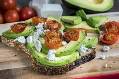 Pane tostato dell'avocado con i pomodori ciliegia ed il feta Fotografie Stock