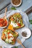 Pane tostato dell'avocado, dell'uovo affogato e del pomodoro fotografie stock