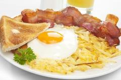 Pane tostato dell'uovo fritto della pancetta affumicata delle patate tritate della prima colazione Immagini Stock