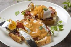 Pane tostato di Benedict delle uova, prosciutto, uova affogate e h butirrosa deliziosa Immagini Stock