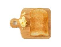 Pane tostato e burro su un tagliere di legno, fondo bianco Immagini Stock