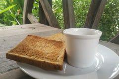 Pane tostato e caffè affettati del pane nero sul piatto bianco fotografie stock libere da diritti