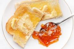 Pane tostato e marmellata d'arance imburrati caldi immagine stock