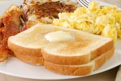 Pane tostato imburrato con pancetta affumicata e le uova Fotografia Stock Libera da Diritti