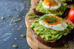 Pane tostato vegetariano con l'uovo e l'avocado fotografia stock