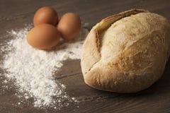 Pane, uova e farina su un piano d'appoggio di legno immagine stock libera da diritti