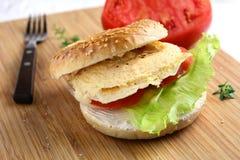 Panecillo del desayuno con el huevo revuelto y las verduras Foto de archivo libre de regalías