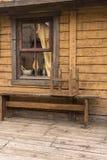 Panecillos que cuelgan en la ventana de una casa del pueblo Banco delante de la casa fotografía de archivo
