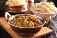 Paneer Butter Masala in a brass bowl on a wooden panel. Royalty Free Stock Images