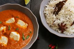 Paneer Butter masala and cooked rice Indian Curry Dinner Royalty Free Stock Image