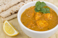 Paneer Makhani. Or Shahi Paneer (Paneer Butter Masala) - Indian curd cheese curry served with chapatis and a wedge of lemon Royalty Free Stock Photo