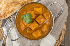 Paneer Makhani or Shahi Paneer. (Paneer Butter Masala) - Indian curd cheese curry in a balti dish, served with naan bread and garnished with coriander leaves Royalty Free Stock Images