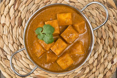 Paneer Makhani or Shahi Paneer. (Paneer Butter Masala) - Indian curd cheese curry in a balti dish, served with naan bread and garnished with coriander leaves Stock Image