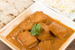 Paneer Makhani or Shahi Paneer. (Paneer Butter Masala) - Indian curd cheese curry served garnished with coriander leaves and served with pilau rice and chapatis Stock Photography