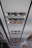 Panel in an airplane above seats stock image