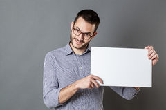 Panel announcement for smiling man with beard and eyeglasses. Panel announcement - smiling young man with beard and eyeglasses holding a blank banner for copy Royalty Free Stock Image