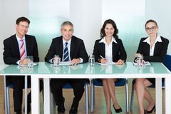 Panel of corporate personnel officers. Sitting at a table stock images