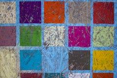 Panel de fibras de madera con la pintura de peladura azul y los cuadrados multicolores brillantes Textura de la superficie ?spera fotografía de archivo libre de regalías