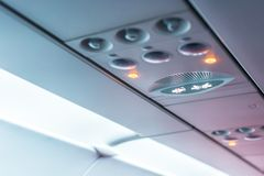 Panel för Closeupflygplankonsol; lampa ljus, behovshjälpknapp, luftvillkor, sefty bälte och inget - röka tända tecknet royaltyfri foto