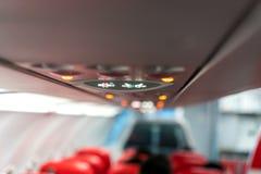 Panel för Closeupflygplankonsol; lampa ljus, behovshjälpknapp, luftvillkor, sefty bälte och inget - röka tända tecknet arkivfoto
