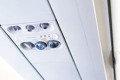 Panel för Closeupflygplankonsol; lampa ljus, behovshjälpknapp, luftvillkor, sefty bälte och inget - röka tända tecknet royaltyfri bild
