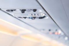 Panel för Closeupflygplankonsol; lampa ljus, behovshjälpknapp, luftvillkor, sefty bälte och inget - röka tända tecknet royaltyfria foton