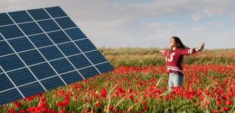 Panel för sol- energi och tonårs- flicka på ett fält med röda vallmo Arkivbilder