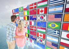 panel with flags, couple fingering one flag Royalty Free Stock Images