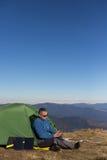 Panel słoneczny dołączający namiot Mężczyzna obsiadanie obok telefonu komórkowego ładuje od słońca Fotografia Stock