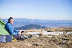 Panel słoneczny dołączający namiot Mężczyzna obsiadanie obok telefonu komórkowego ładuje od słońca Fotografia Royalty Free