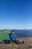 Panel słoneczny dołączający namiot Mężczyzna obsiadanie obok telefonu komórkowego ładuje od słońca Obrazy Royalty Free