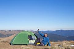 Panel słoneczny dołączający namiot Mężczyzna obsiadanie obok telefonu komórkowego ładuje od słońca Obraz Royalty Free