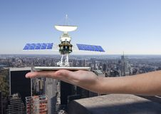 panel słoneczny satelita na ręce z miastem behind Obrazy Stock
