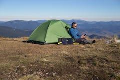 Panel słoneczny dołączający namiot Mężczyzna obsiadanie obok telefonu komórkowego ładuje od słońca Zdjęcie Royalty Free