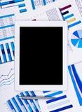 Panel táctil sobre cartas y gráficos de papel financieros Fotografía de archivo libre de regalías