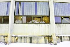 Panel wall of abandoned administrative building with broken glass in windows and boarded up with rusty metal plates. Snowy winter street, horizontal background stock image