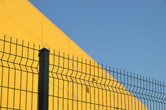 Panel wire fence. Green panel wire fence sweep a yellow building Stock Photography