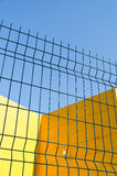 Panel wire fence. Green panel wire fence sweep a yellow building Stock Photos