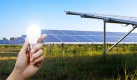 Paneler för sol- energi och ljus kula i handen, energi Arkivfoto