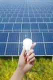 Paneler för sol- energi och ljus kula i handen, energi Arkivbild